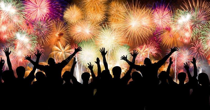 Группа людей наслаждаясь эффектными фейерверками показывает в масленице или празднике стоковые фотографии rf