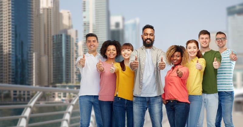 Группа людей показывая большие пальцы руки вверх в Дубай стоковое изображение
