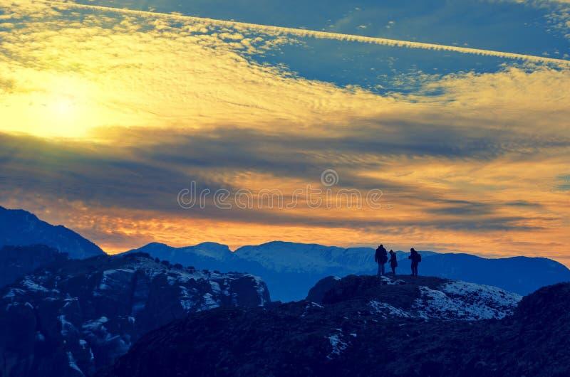 Группа людей стоит на верхней части утеса Красивое clou захода солнца стоковая фотография