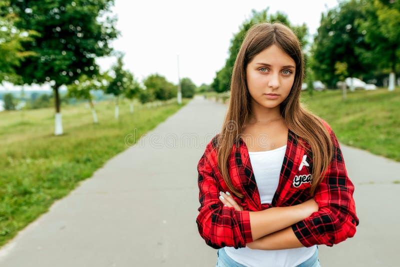 Грустная девушка в красной рубашке Лето в городе на предпосылке дороги Открытый космос для текста Осадка, грустная стоковое изображение rf