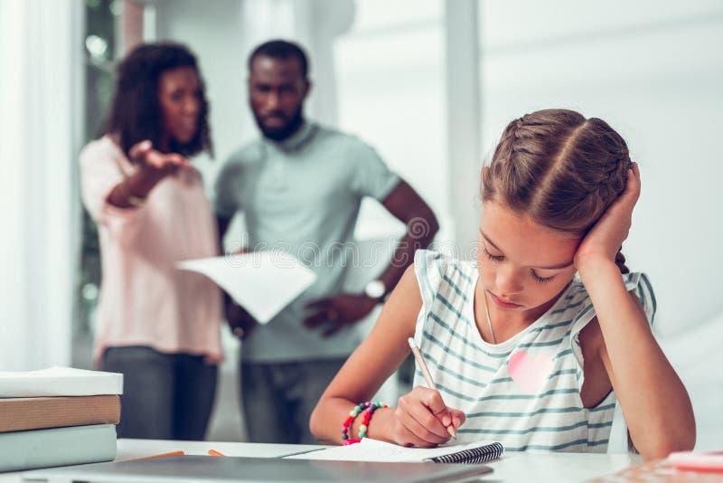 Грустная дочь делая домашние задачи пока родители кричащие на ей стоковое изображение