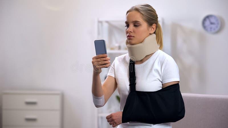 Грустная женщина в сообщении чтения слинга воротника и руки пены цервикальном на смартфоне стоковые фотографии rf