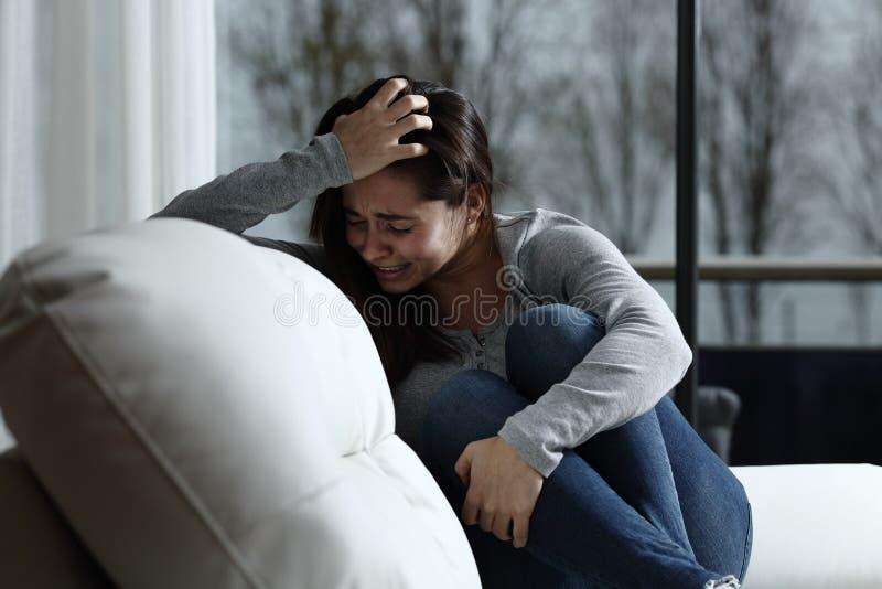 Грустная женщина жалуясь и плача дома стоковое фото rf