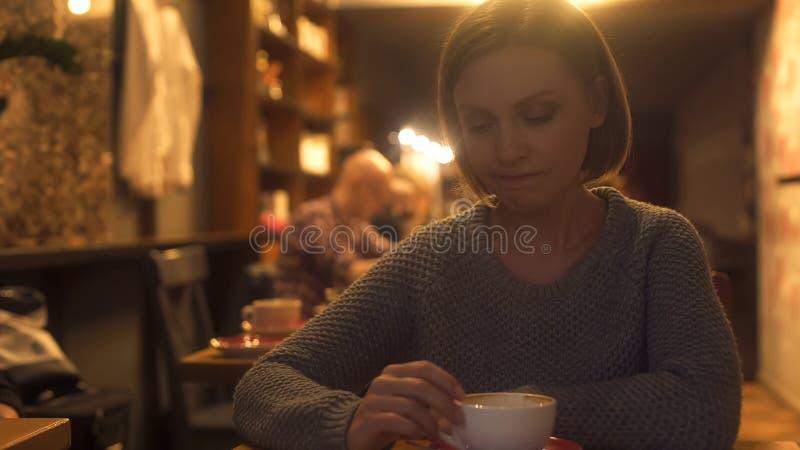 Грустная женщина сидя в кафе, тягостно испытывая для того чтобы прекращать, одиночество, кризис стоковые изображения