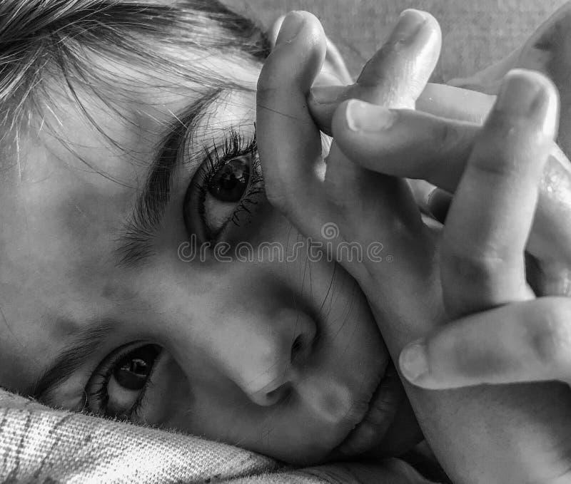 Грустная или сердитая маленькая девочка кладя вниз стоковые изображения