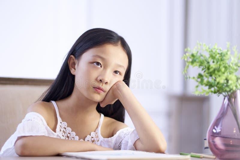 Грустная маленькая азиатская девушка сидит на мысли стола стоковая фотография rf