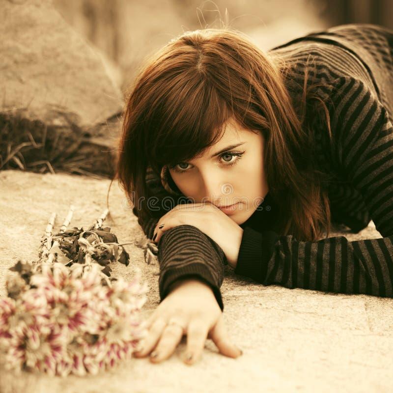 Грустная молодая женщина лежа на надгробной плите стоковые фотографии rf
