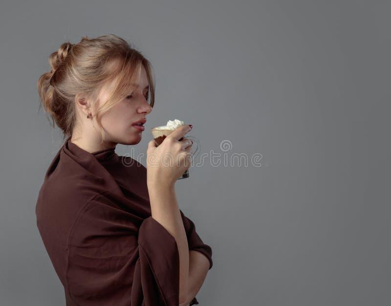 Грустная молодая красивая женщина с кружкой горячего шоколада стоковые фото