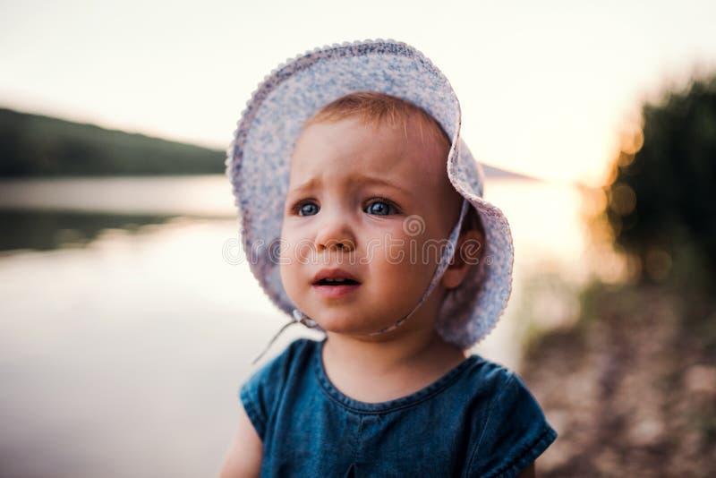 Грустная небольшая девушка малыша стоя outdoors рекой летом стоковая фотография