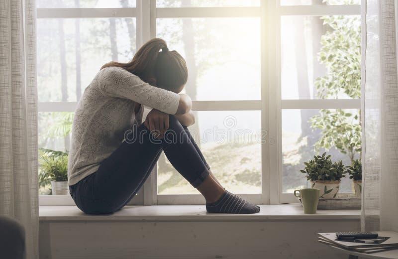 Грустная сиротливая женщина сидя дома самостоятельно стоковая фотография rf