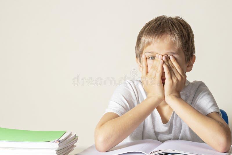 Грустная уставшая расстроенная сторона заволакивания школьника с его руками сидя около таблицы с кучей учебников и тетрадей стоковое фото