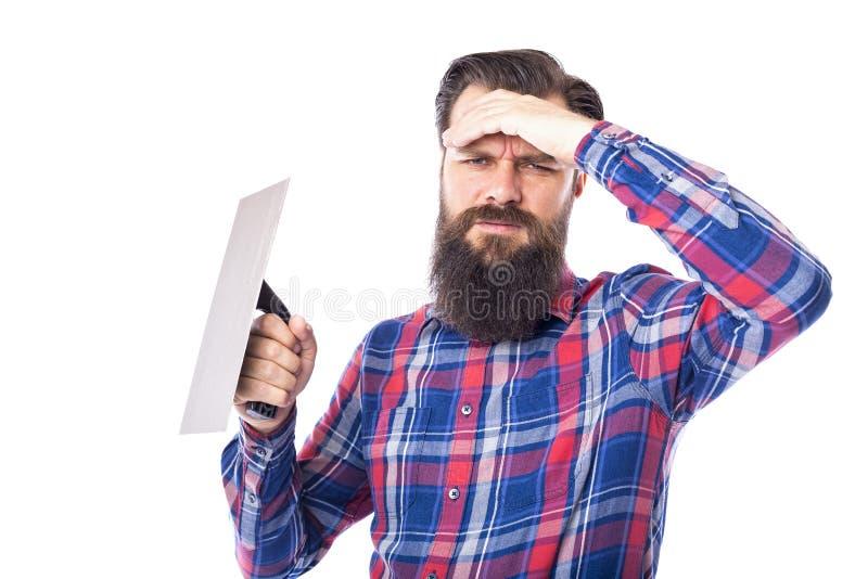 Грустное бородатое удерживание человека использовало инструмент masonry стоковое фото
