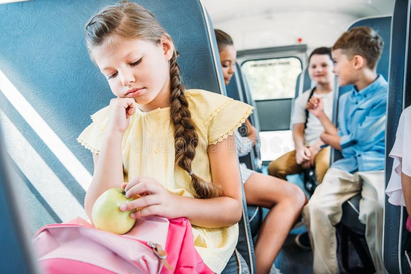 грустное маленькое катание школьницы на школьном автобусе пока ее запачканный беседовать одноклассников стоковые изображения rf