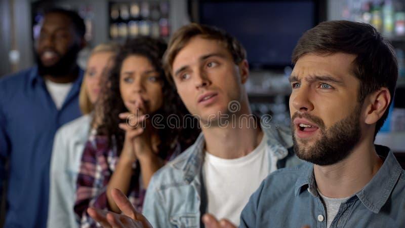Грустные болельщики наблюдая спичку в баре, молодых зрителях смотря разочарованный стоковое изображение rf