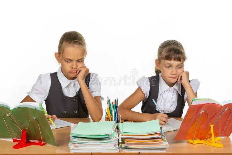 Грустные школьницы смотрят книгу в уроке стоковое изображение rf