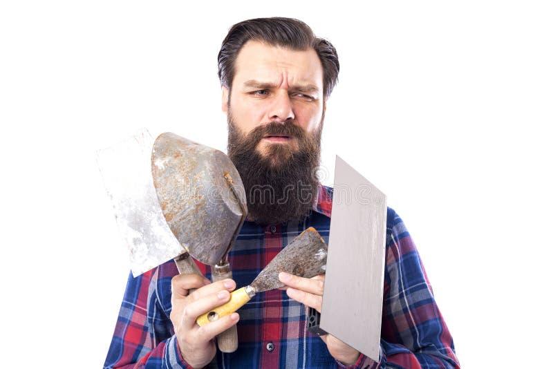 Грустный бородатый человек держа используемые инструменты masonry изолированный на белизне стоковые фото