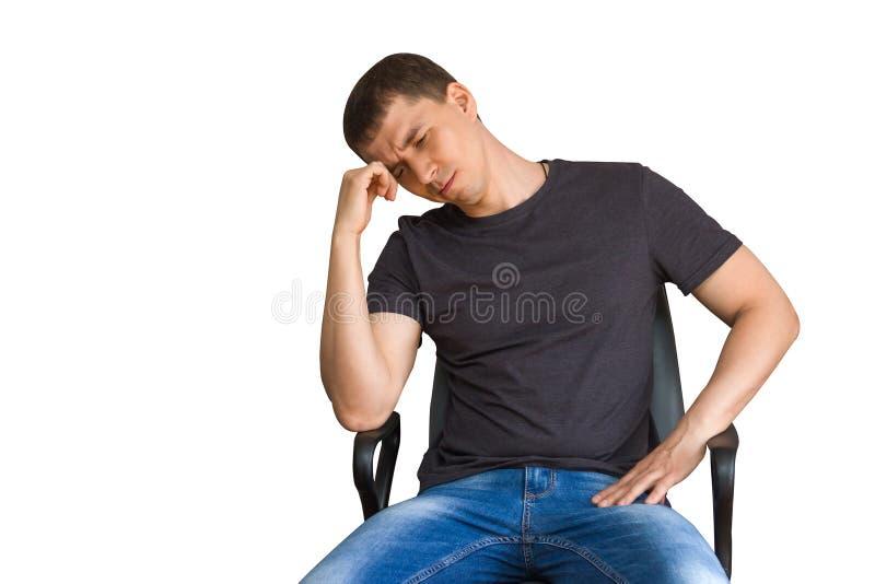 Грустный внимательный молодой человек сидя на стуле, подпирая вверх голову с его рукой, изолированной на белизне стоковые изображения