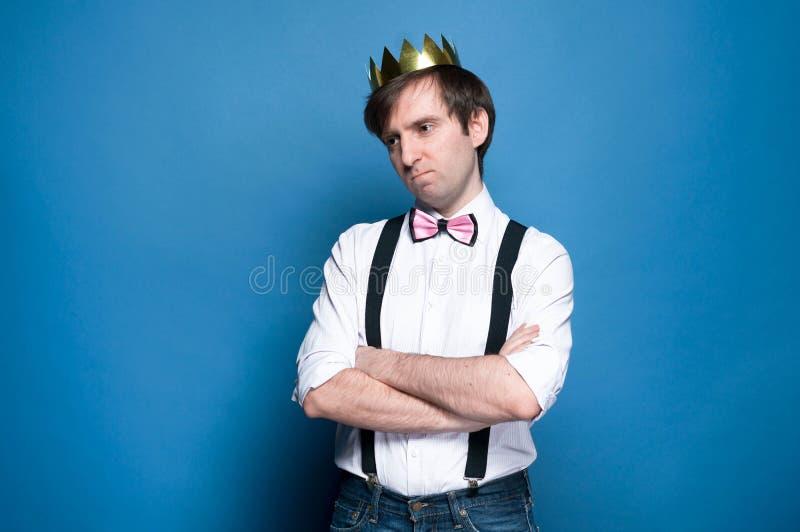Грустный красивый человек в рубашке, подтяжк, бабочке и золотой кроне  стоковые фото