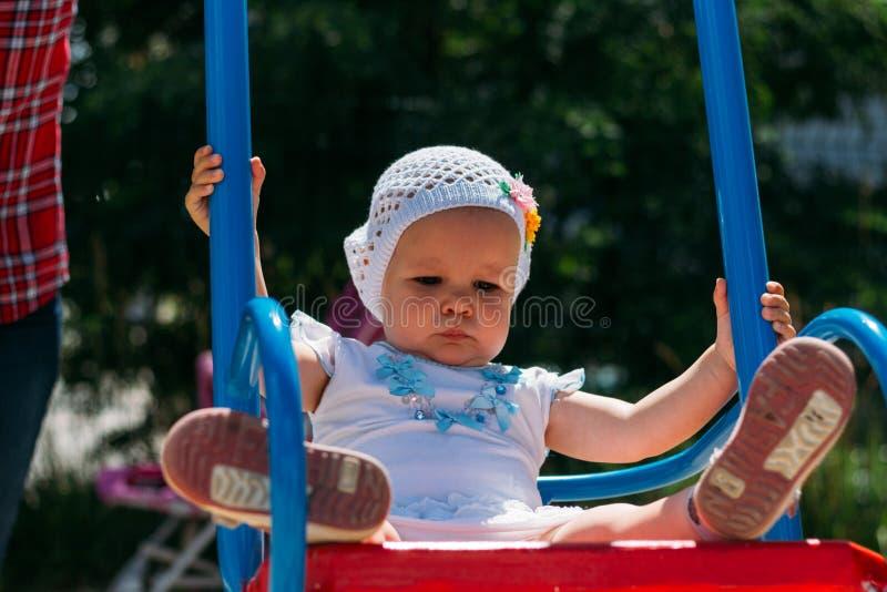 Грустный, маленькая девочка в белом платье и шляпа, ехать на качании, солнце лета и жаре Спортивная площадка детство, спокойствие стоковое фото rf