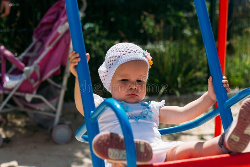 Грустный, маленькая девочка в белом платье и шляпа, ехать на качании, солнце лета и жаре Спортивная площадка детство, спокойствие стоковая фотография rf
