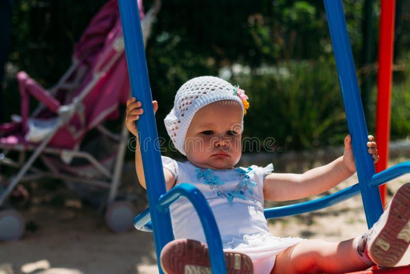 Грустный, маленькая девочка в белом платье и шляпа, ехать на качании, солнце лета и жаре Спортивная площадка детство, спокойствие стоковое изображение rf