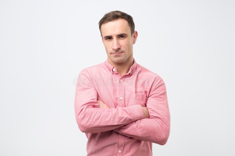 Грустный несчастный молодой человек в розовой рубашке имеет сварливое выражение после ссоры с женой стоковые изображения rf