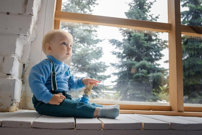 Грустный, но красивый голубоглазый младенец сидя на windowsill и не смотря камеру стоковое изображение