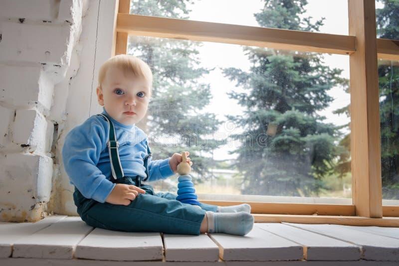 Грустный, но красивый голубоглазый младенец сидя на windowsill и смотря камеру стоковые фото