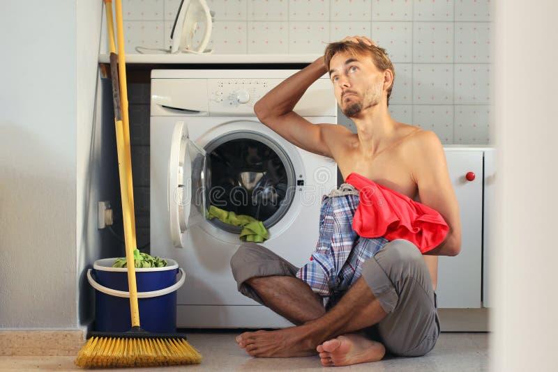 Грустный, озадаченный человек взгляда нагружает прачечную в стиральную машину Мужская домохозяйка, концепция холостяка стоковое фото rf