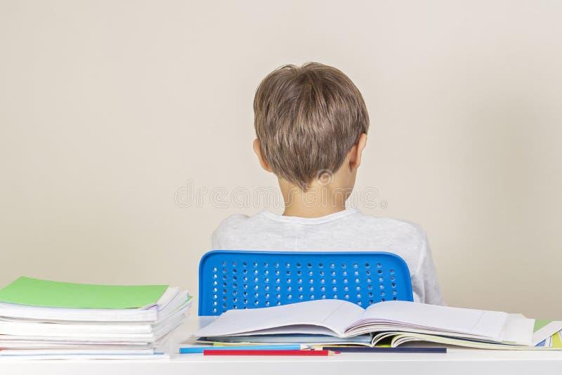 Грустный самостоятельно сидеть ребенк поворачивает назад на таблицу с кучей учебников и тетрадей стоковая фотография rf