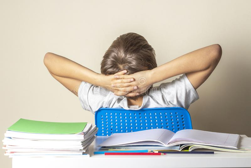 Грустный самостоятельно сидеть ребенк поворачивает назад на таблицу с кучей учебников и тетрадей стоковое фото rf
