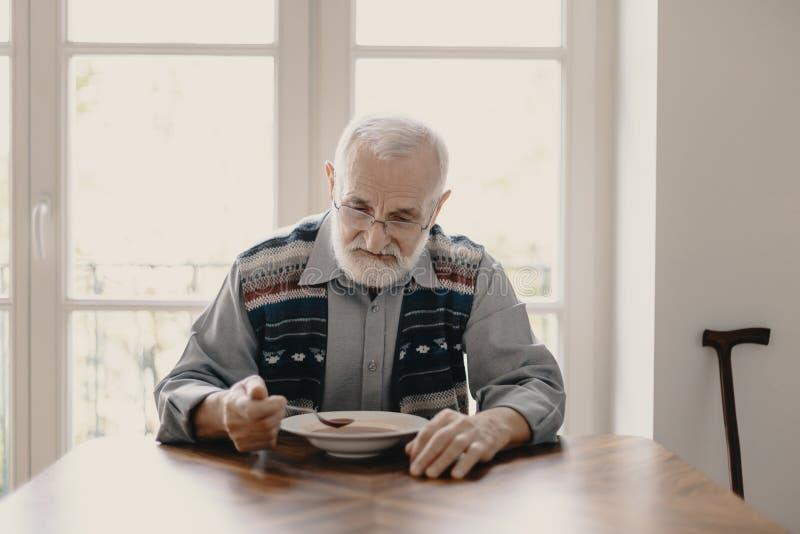 Грустный сиротливый старший человек есть суп в пустой квартире стоковое изображение