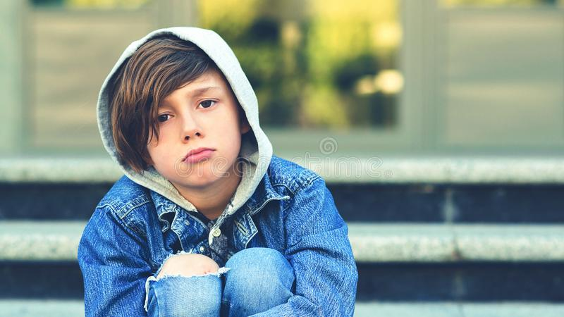 Грустный школьник сидя на лестницах outdoors Несчастный мальчик в куртке джинсовой ткани с клобуком и выскобленным коленом Концеп стоковые изображения rf