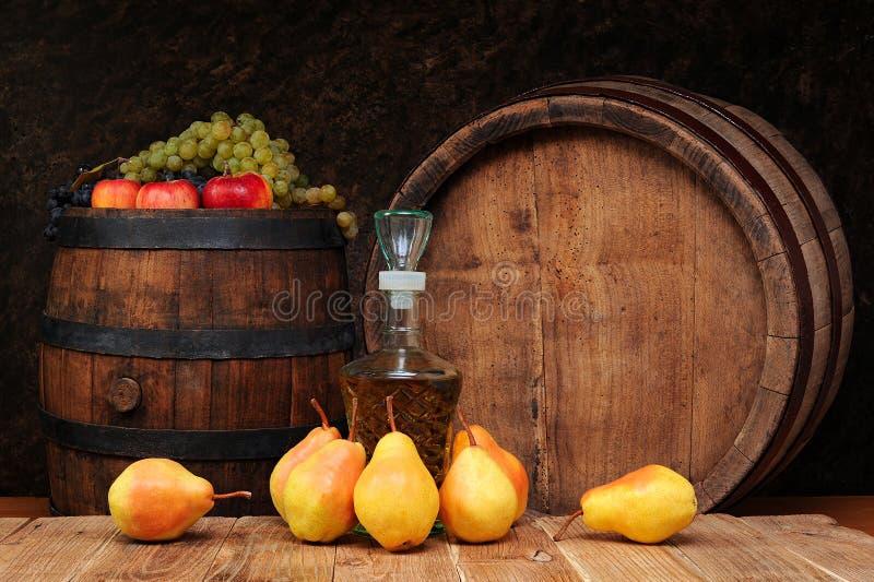 Груши, деревянный бочонок и бутылка рябиновки стоковое изображение rf