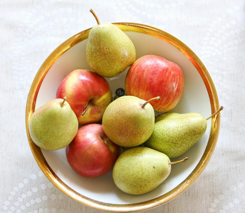 Груши и яблоки на плите стоковое изображение
