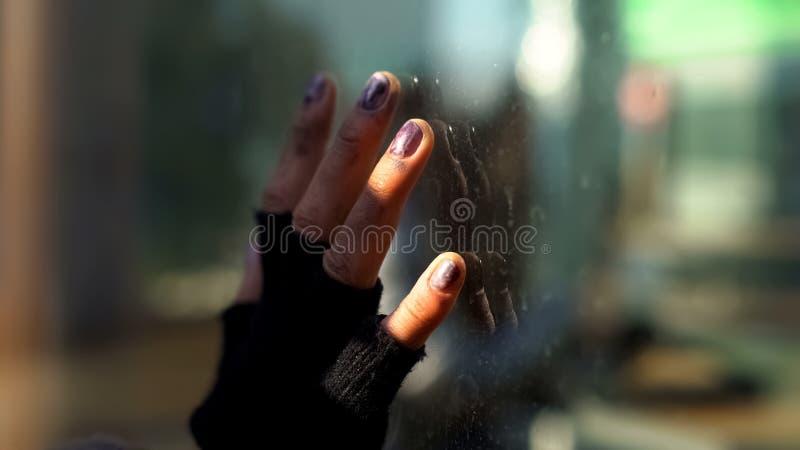 Грязная бездомная рука на стекле окна, социальная несправедливость, плохое убежище, безвыходность стоковые изображения rf