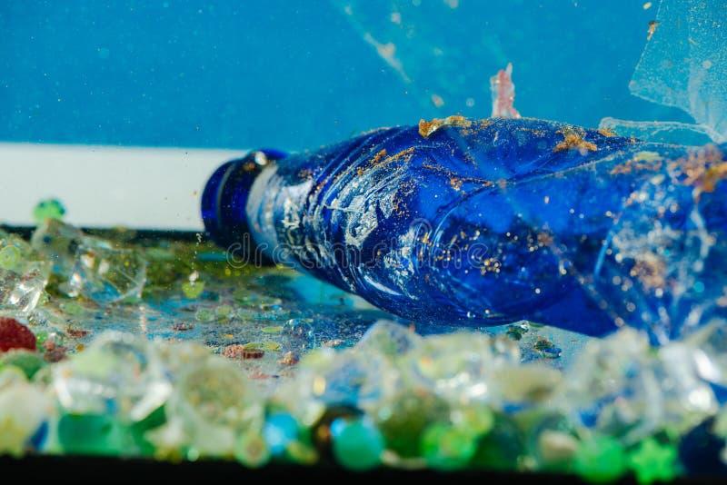 Грязная голубая скомканная бутылка будучи покрыванным с пылью и ржавч стоковое фото