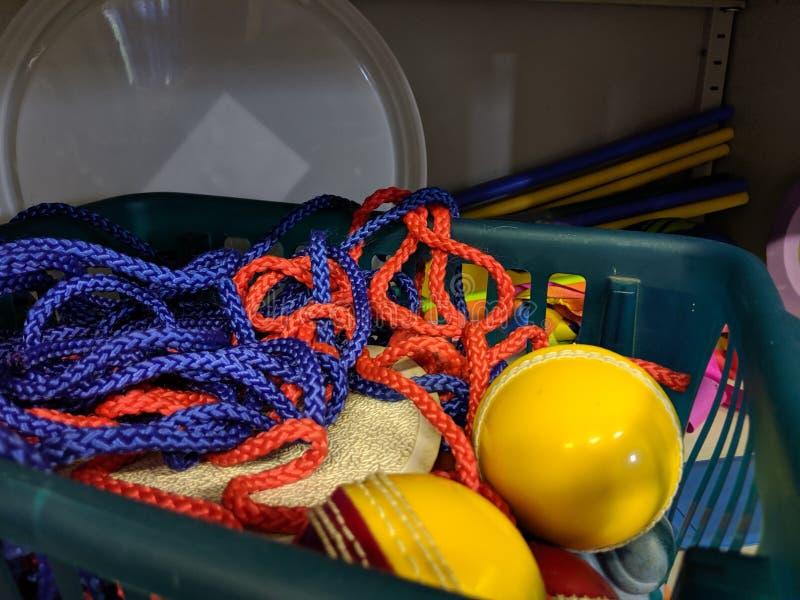 Грязная дезорганизованная корзина покрашенной веревочки шнура в кухонном шкафе хранения игр школы стоковое фото