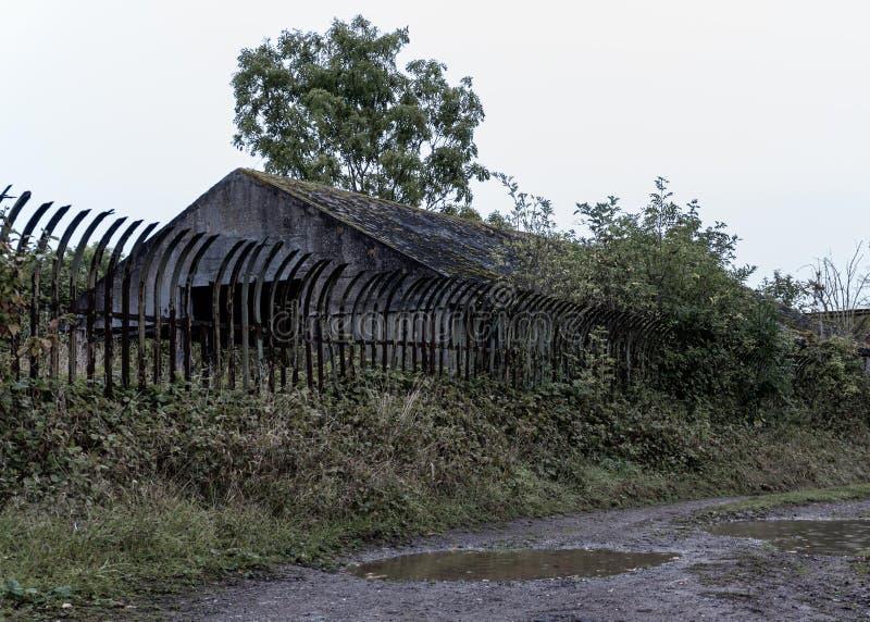 Грязная тропа рядом с заброшенными зданиями Защищено высокометаллическим ограждением Саксонс Лоде Нефтяное хранилище, Ворчестерши стоковая фотография rf