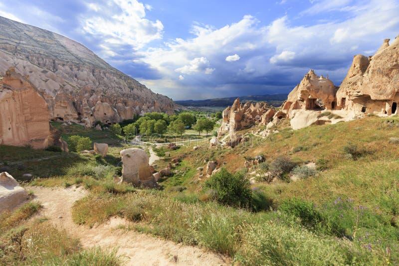 Грязная улица извивается между коническими пиками утесов, старых пещер против фона ландшафта горы долины внутри стоковое фото