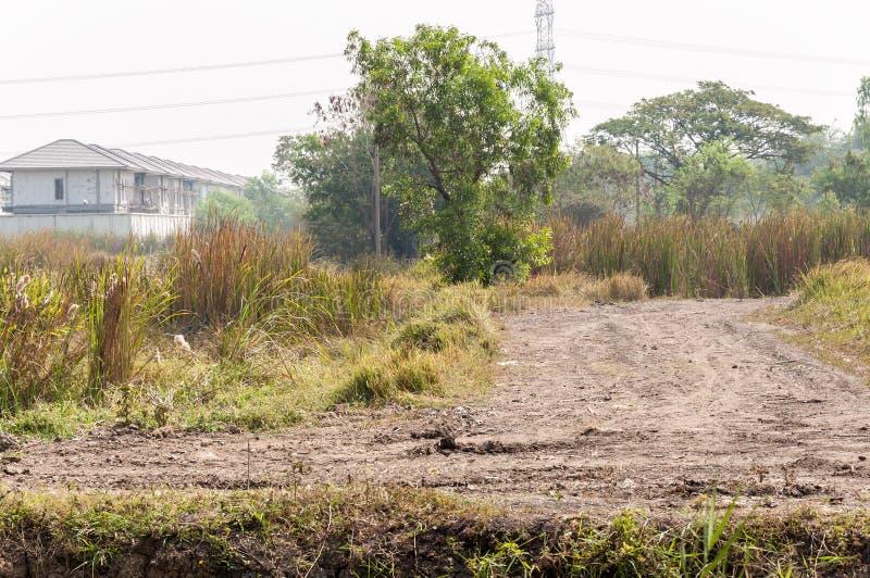 Грязная улица через поле травы к строительной площадке стоковое фото