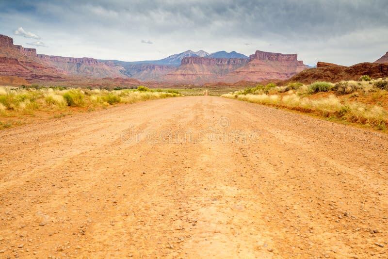 Грязная улица через красивую непроизводительную землю стоковое изображение