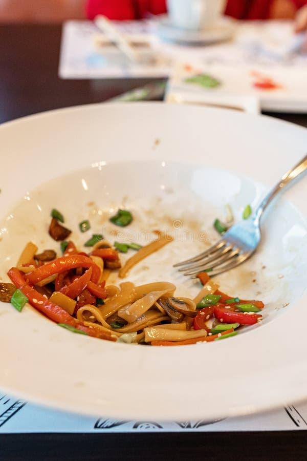 Грязные блюда соус смазанный на плите остатки, макаронные изделия, ресторан не закончил клиентов взгляд со стороны, вертикаль стоковое фото rf