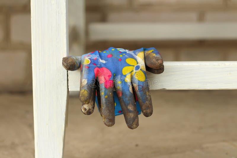 грязные красочные перчатки вися на поперечине таблицы стоковая фотография rf