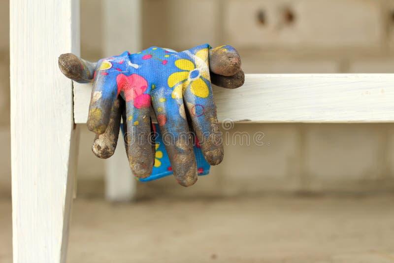 грязные красочные перчатки вися на поперечине таблицы стоковые изображения rf