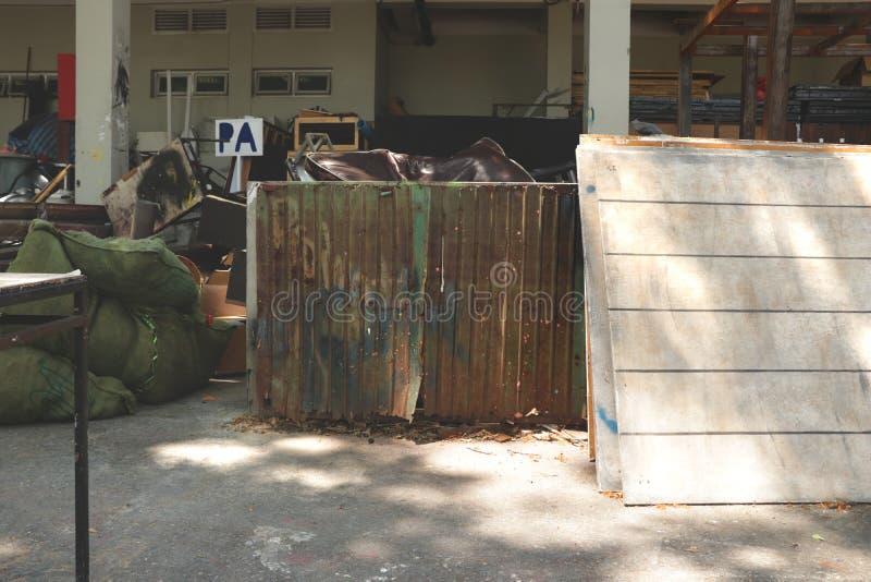 Грязный внешний JunkYard с ржавыми старыми дверями цинка, белизна задворк гаража студии покрасил древесины и мешки зеленого цвета стоковые изображения