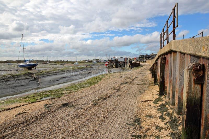 Грязный пляж во время отлива с причаленными рыбацкими лодками вдоль лимана Темза, Leigh на море стоковые изображения rf