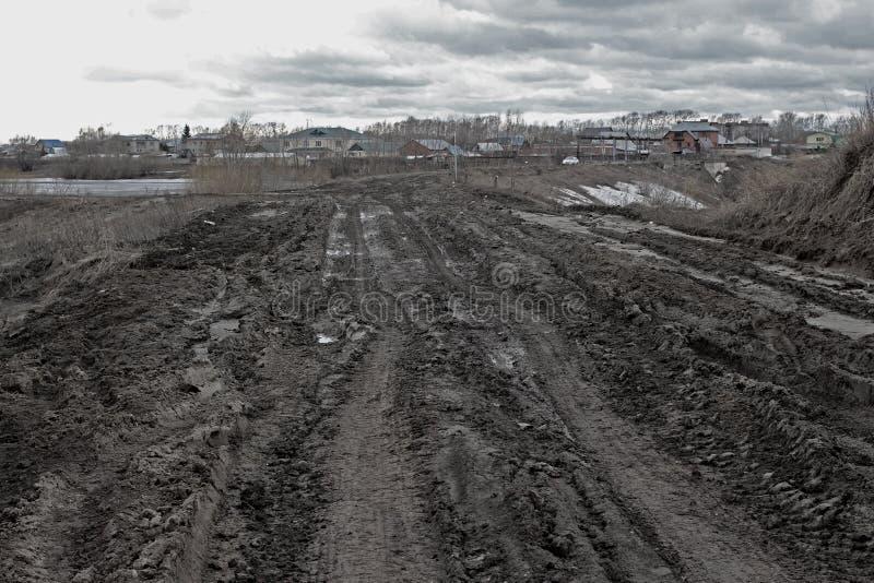 Грязный смазал дорогу плохая погода дороги непроходимое направление к деревне сибирской деревни в России стоковая фотография rf