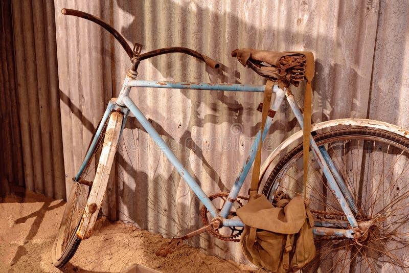 Грязный старый заржаветый велосипед полагаясь против сарая олова стоковая фотография rf
