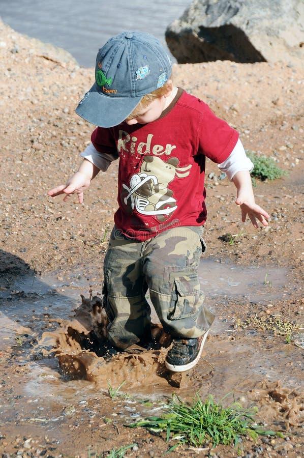 грязь мальчика играя лужицу стоковая фотография
